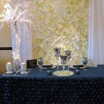 White and Ivory Flower backdrop with white sheer drapes, crystal chandelier, Crystal Tree and slate blue floral sweetheart table.