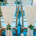 Chiavari chairs with sheer draping tied back with succulents