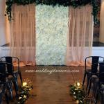 Silk flower wall with gold drapes and live eucalyptus trim