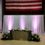 8 foot white satin drape sweetheart table  backdrop with 15 foot drapes on the sides covering maps at Planes of Fame Chino Hills.