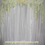 Our silk flower valance with gold Love sign with white sheer drapes